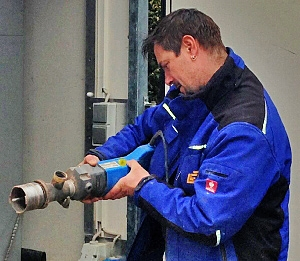 VDE-Prüfplakette wird auf Bohrmaschine geklebt